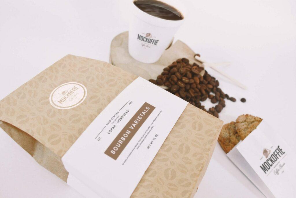 Kit de mockups para presentar marca de café, que incluye una bolsa, una taza para llevar y una bolsa de papel para galletas